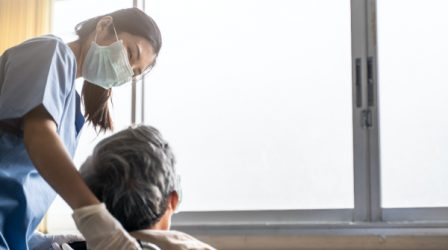 Asian nurse taking care of mature male patient sitting on wheelchair in hospital. Young woman and old man wearing surgical face mask for protection of covid 19 pandemic. Girl smile to elderly man.