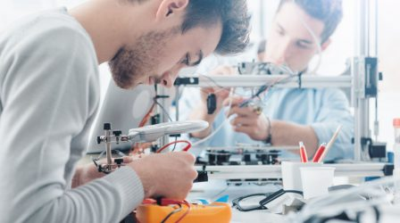 Engineering students working in the lab, a student is using a voltage and current tester, another student in the background is using a 3D printer