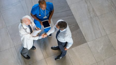 High angle view of senior doctor shaking hands to representative of pharmaceutical companies. Top view of businessman shaking hands with physician in a hospital. Businessman conclude an agreement with doctor.