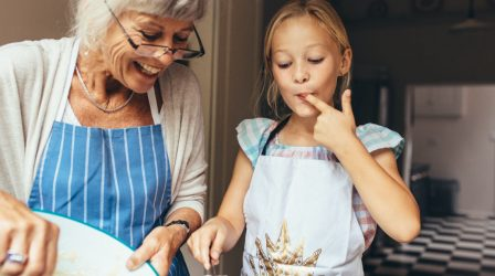 Senior woman in apron making batter for cake. Little girl tasting cake batter standing in kitchen with grandmother.