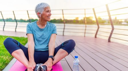 Senior woman exercising in park while listening to music. Senior woman doing her stretches outdoor. Athletic mature woman stretching after a good workout session.