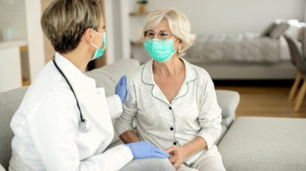 Happy mature woman and female doctor wearing protective face masks during a home visit.