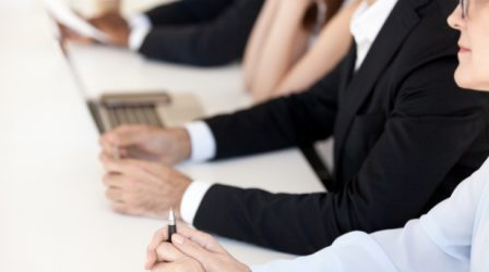 Close up of office employees sit in row listening to candidate or applicant talk at interview, diverse workers attentive considering or pondering , businesspeople hands at desk at meeting or briefing